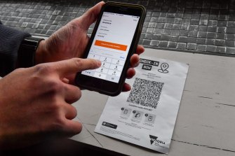 A person scans a QR code using the Services Victoria check-in app.