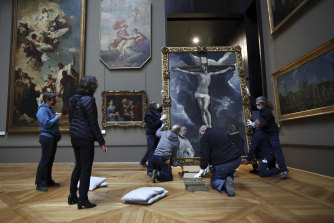 Workers handle a painting called 'Christ on the Cross Adored by Two Donors' by Spanish painter El Greco amid works at the Louvre.