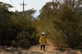 NSW RFS  volunteers in Tahmoor walk out of the bush after checking on the fire, which is a part of the Green Wattle Creek blaze.