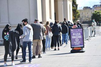 People queue to be vaccinated at the Royal Exhibition Building in Carlton on Saturday.