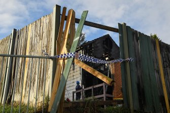 Police investigate the scene of the fatal blaze on Wednesday.