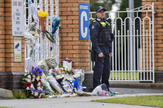 An officer stands guard outside the Victoria Police academy following the private funeral for Senior Constable Kevin King on Friday afternoon.