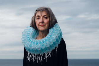 Sydney artist and designer Ruth Downes wears a collar of masks that she made to illustrate the impact on the environment of single-use items.