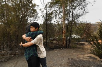 Gabriel hugs his mother, Helena, after returning to their burnt home at Balmoral.