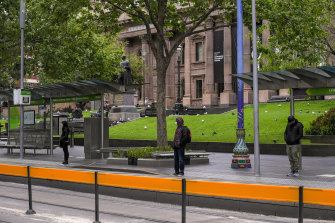 Passengers socially distance while waiting for a tram on Swanston Street on Monday.