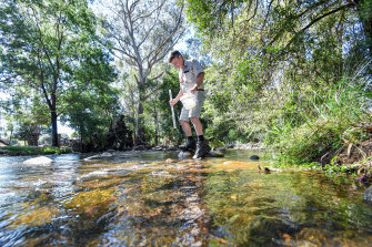 Rod Falconer testing the water where the creek runs through his property.
