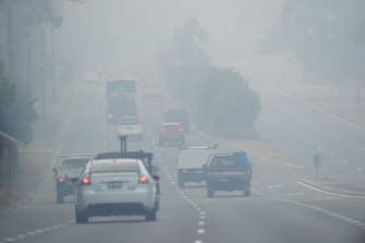 Cars drive through smoke haze along Forest Way, Belrose, on Friday.