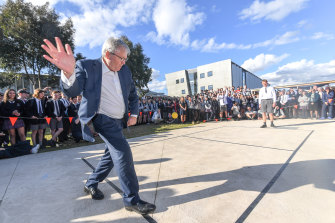 Former prime minister Kevin Rudd playing handball against McKinnon Secondary College champ Ash Hunter.