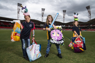 Pony Club members Abbie, 9, Sophie, 11, and Lilah, 7, hold the showbags they have help inspect.