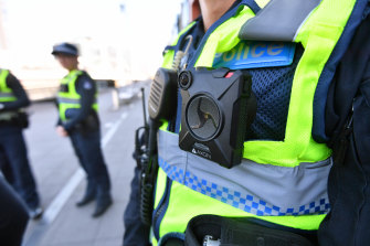 A police officer wears a body-worn camera.