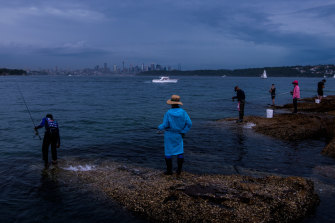Fishing at Laings Point in Watsons Bay as a summer storm tracks over Sydney from the west.