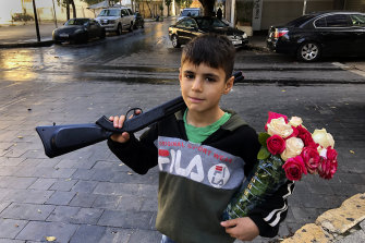 A displaced Syrian boy, Omar, 10, holds a toy gun while selling flowers on the street in Beirut, Lebanon.