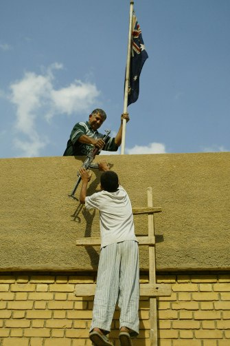 Australian embassy employee Kareem Challur holds the Australian flag and takes an AK-47 from his son Thaer, 13, on the rooftop of the embassy, which they protected in 2003.