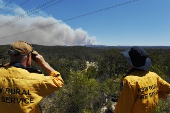 NSW RFS members watch the Gospers Mountain fire move south-east on Thursday.