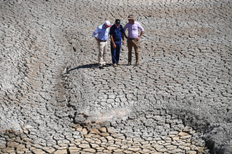 Treasurer Josh Frydenberg, orchard owner Dino Rizzato and Water Resources Minister David Littleproud in a dried-up dam at Cottonvale apple orchard, outside the drought-ravaged town of Stanthorpe, 180km south-west of Brisbane.