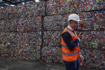 Matt Kean, the Energy and Environment Minister, stands in front of bales of aluminium cans - about 10,000 in each - that will be recycled.