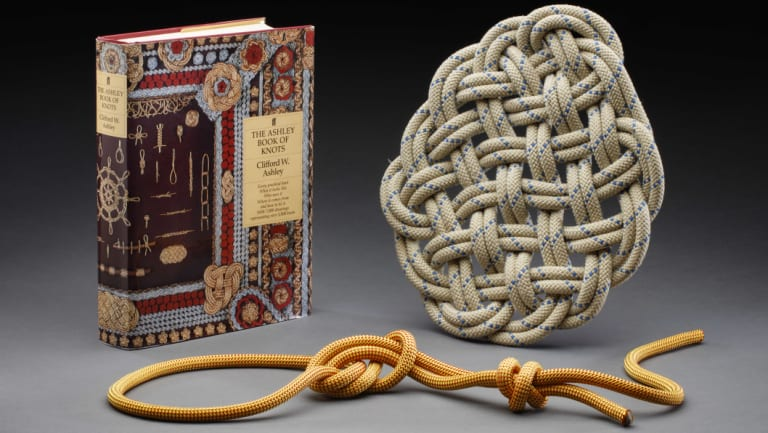 Craig Challen's The Ashley Book of Knots, and a knotted rope and large flat knot.