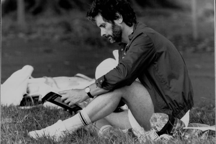 A cricket game between authors and publishers at Centennial Park in 1987. James Cowan reads while awaiting his turn to bat.