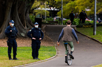 A man rides a unicycle past police in the CBD exclusion zone on Saturday.