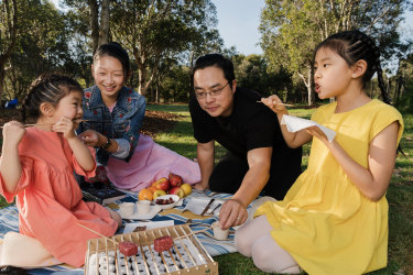 Alina Van and Raymond Hau with their daughters Arielle 4 and Ariana 9  at Sydney Park in Alexandria. Alina and Ray own Firepop - a pop up truck/food van specialising in charcoal grilled meats. Photographed Thursday 23rd September 2021. Photograph by James Brickwood. SMH NEWS 210924