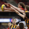 Melbourne's Luke Jackson fends off a pair of Hawks.