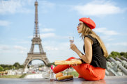 Young woman in red cap having a picnic with glass of wine and baguette sitting in front of the Eiffel tower in Paris iStock image for Traveller. Re-use permitted. Why we still love France by Ute Junker