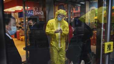 A medical worker checks customers' temperatures as they enter a store in Beijing.