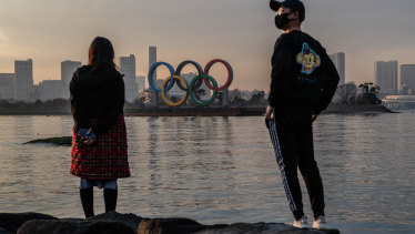 A woman and a  man wearing a face mask view the Olympic Rings on January 22, 2021 in Tokyo, Japan.