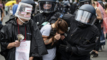 Police arrest a demonstrator at an unannounced demonstration at the Victory Column, in Berlin.