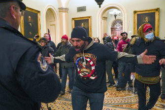 Online fury and disinformation, like the QAnon conspiracy theory signified on the rioter's jumper, was given physical form when rioters stormed the US Capitol.