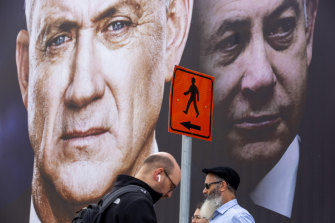Pedestrians pass an election campaign billboard with photos of Benny Gantz, left, and Benjamin Netanyahu in Ramat Gan, Israel.
