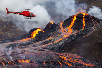 A helicopter flies close to a volcanic eruption which has begun in Fagradalsfjall near the capital Reykjavik on March 20, 2021 in Fagradalsfjall, Iceland.