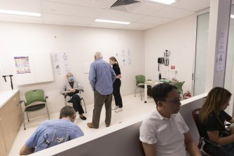 Patients sit in a waiting area after recieving the COVID-19 AstraZeneca vaccine at the Sydney West COVID vaccination centre in Olympic Park.