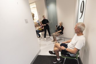 John Seitz and Heather Griffiths sit in a waiting area after receiving the AstraZeneca vaccine at a vaccination centre in Olympic Park.