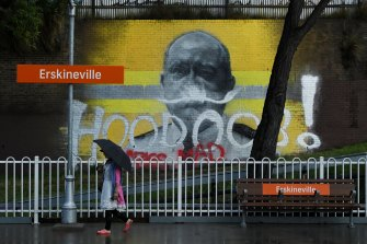 A woman stands near a mural at Erskineville station depicting former RFS chief Shane Fitzsimmons  that has been graffitied for a second time.