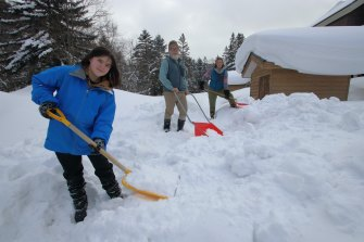 Grace, John and Lucy Morrell at their home in Hokkaido, Japan, digging out their storage shed in preparation for moving back to Australia.