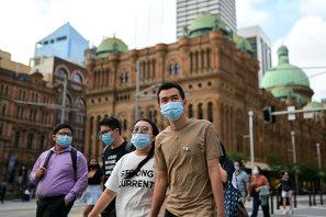 Pedestrians wearing face masks in Sydney's CBD on Thursday.