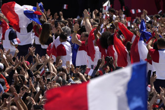 Fans wave French flags and cheer in the Olympics fan zone at Trocadero Gardens in front of the Eiffel Tower in Paris on Sunday.