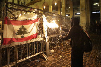 A protester uses an aerosol can to blast fire at police in Lebanon's capital.