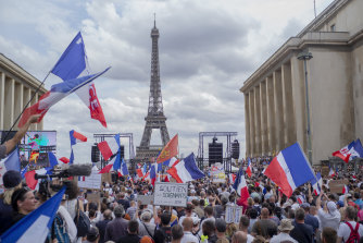 Thousands gather at Place Trocadero near the Eiffel Tower, Paris, to protest against the COVID-19 pass which grants vaccinated individuals greater ease of access to venues.