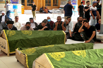 Mourners pray near the coffins of coronavirus patients who were killed in a hospital fire, in Najaf, Iraq.