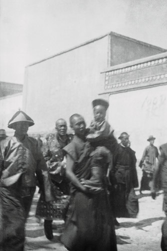 An attendant carries the new Dalai Lama, aged five or six in this photo (which dates it to around 1940), as he prepares to journey across the Himalayas to Lhasa, Tibet. Years later, he would flee to north India.