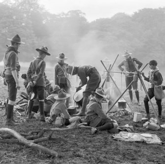 British Scouts prepare dinner at an outdoor camp, circa 1910.