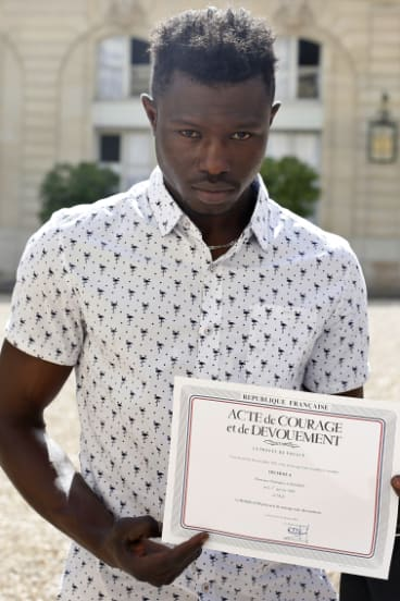 Gassama with a certificate of courage and dedication.