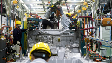Workers assemble a vehicle at the Xiaopeng Motors prototype centre in China.