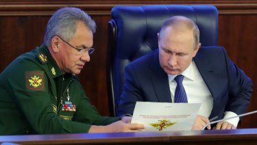 Russian President Vladimir Putin, right, and Defence Minister Sergey Shoigu talk to each other after visiting an exhibition at the Russian military's headquarters as part of a conference on the Russian campaign in Syria.