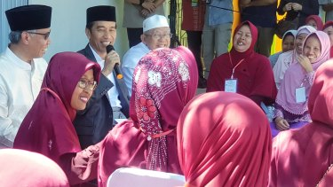 Joko Widodo addresses residents in Serang, Banten, accompanied by the chairman of the Financial Services Authority, Wimboh Santoso, and the head of Indonesian Ulema Council Ma'ruf Amin.