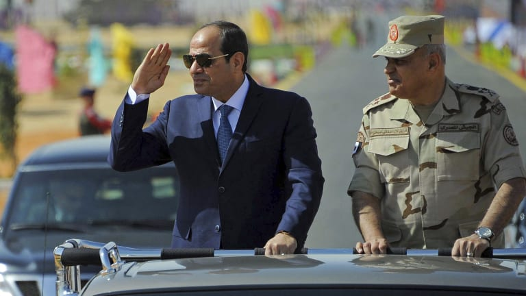 Egyptian President Abdel-Fattah el-Sissi salutes as he inspects troops with Minister of Defence Sedki Sobhy, in Suez, Egypt.