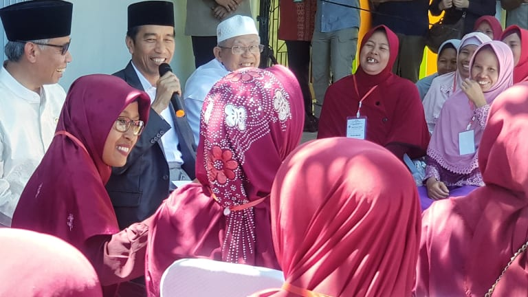 Joko Widodo addresses residents in the town of Serang, in Banten province, accompanied by the chairman of the Financial Services Authority, Wimboh Santoso, and the head of the Indonesian Ulema Council, Ma'ruf Amin.