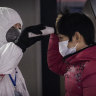 A Chinese health worker checks the temperature of a woman entering a subway station in Beijing.